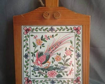 Hanging kitschy 1970s wooden trivet with decorative bird tile