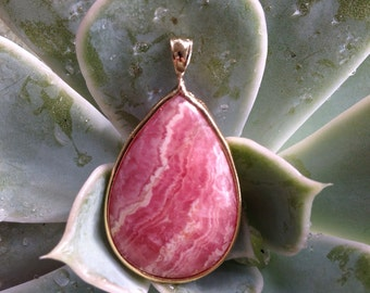 Pear shaped Rhodochrosite cabochon bezel set into gold filled pendant.