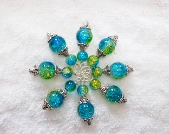 Set of 8 handmade stitch markers in blue and green tones.