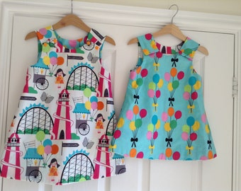 Girls Reversible pinafore dress balloons and fairground sizes 0-3 months up to 4-5yrs