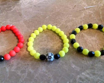 Kids bead bracelets.  Sample of two soccor and one plain. Can request any colors and other sports balls besides soccor. Party favors,