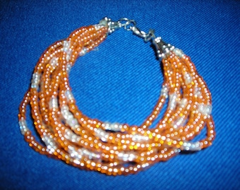 "6.5"" 10 Strand orange and white beaded bracelet."