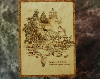 Lighthouse seascape with jutting rocks and cliffs woodburned on pine with Seagulls flying in a background of trees
