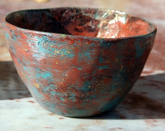 paper mache bowl in patinas of brick red and turquoise blue with gold leaf flecks