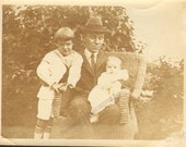 Handsome Man Sits in Wicker Chair and Hold a Baby Young Boy Stands Beside Him Vintage Photo  K16703