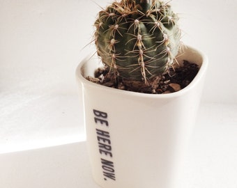 small porcelain planter screen printed be here now black text.