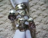 6 Assorted napkin rings handcrafted from antique silverware
