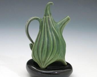 Dark green porcelain teapot on black pillow, small scale, hand built ceramics
