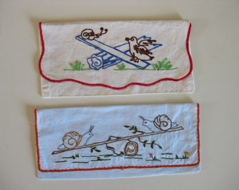 French fabric pouches with embroidered snails on see-saw