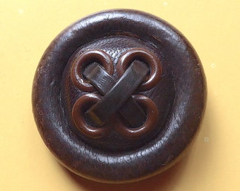 Leather button, vintage.  A rolled border, 4 central brown metal eyelets which are cross banded with resin thongs. pad back. c 1940's.