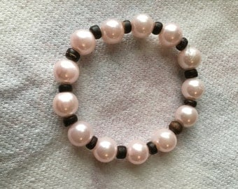 Pink beaded bracelet alternated with little brown wooden beads