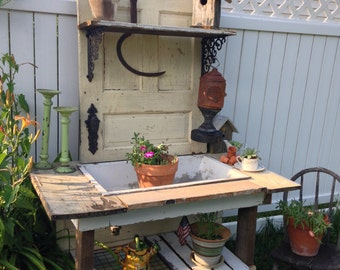 Garden potting bench. Antique old solid door and cast iron sink, with old chippy paint wood frame in original pale yellow