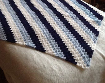 Crocheted lap afghan in blues and white stripes