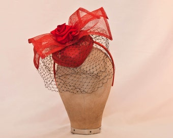 Handmade red heart shaped ladies fascinator/hat decorated with bow and ribbon rose and black veil.