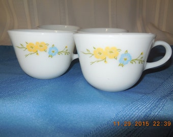 Set of four glass cups by Pyrex, white with yellow and blue flowers.