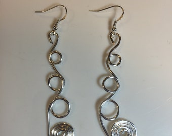 Silver non-tarnish wire earrings with three circles and a big tight spiral on the bottom  hanging on sterling silver french hook earwires.