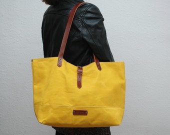 Waxed canvas bag,mustard color, leather handles and closures.UNIXEX
