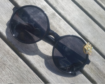 Crown on black round sunglasses.