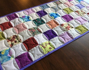 Traditional scrappy quilted table runner/multiple colored blocks/machine quilted with circles/reversible with lavender backing/