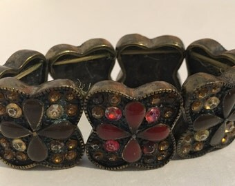 Brass toned stretch bracelet with crystals and enamel flowers