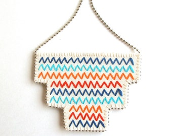 Embroidered geometric necklace zigzags in red orange and blue on bright cream muslin with cream felt back An Astrid Endeavor