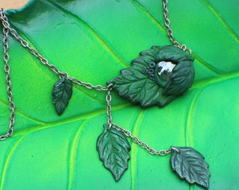 Green sculpted clay leaf necklace with a green glass cabochon