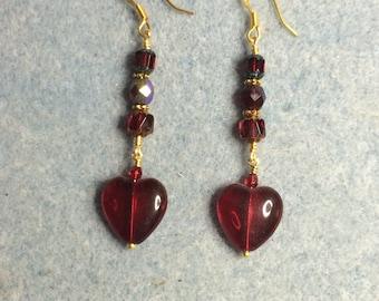 Ruby red Czech glass heart bead dangle earrings adorned with ruby red Czech glass beads.