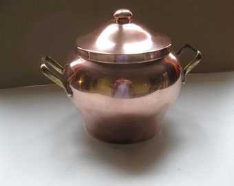 Decorative French lidded copper pan with two brass handles.