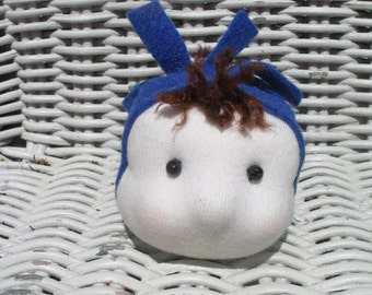 Hand stitched Waldorf face brooch wearing a blue hat.
