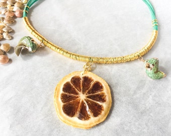 Shell necklace and lemon on golden green