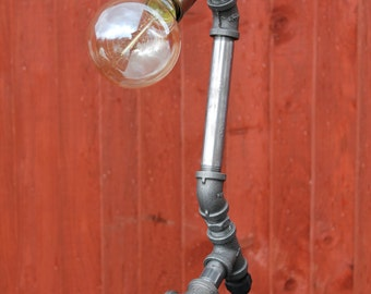 Steampunk pipe light made from industrial pipe fittings featuring an Edison light bulb.