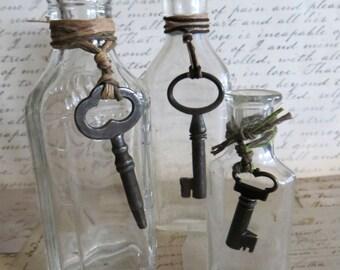 Three Antique Glass Bottles with Skeleton Keys