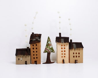 Four buildings of felt, with a tree. Miniature in pale brown colors.