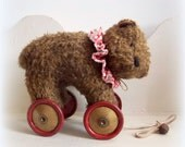 large mohair bear on vintage red gold Meccano wheels