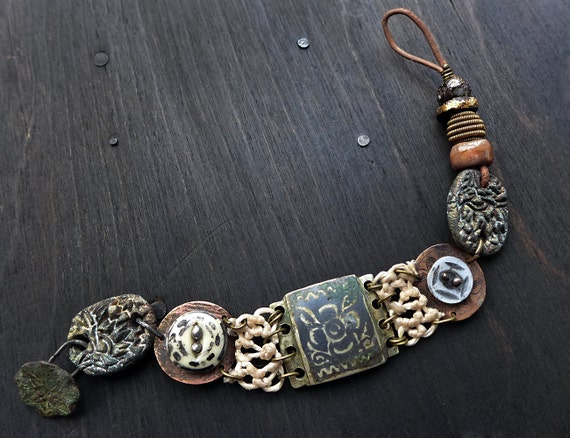 Tectonic. Tribal assemblage bracelet with antique buttons and artisan beads. Primitive mixed media jewelry.