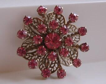 Vintage unmarked foil backed dimensional pink faceted rhinestone prong set goldtone over silver filigree brooch pin