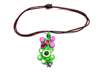 A pendant made of various buttons and a green lace on a burgundy suede cord.