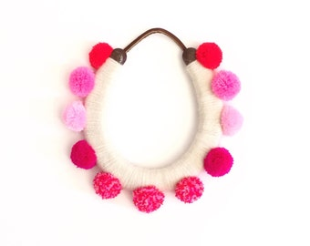lucky yarn wrapped horseshoe with pink pom poms