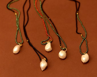 Long multi color chain necklace with a big crude freashwater pearl.