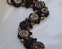 Bracelet / Antique black glass buttons and fire-polished glass beads / Flower and snow flake pattern buttons