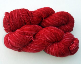 Hand dyed red and pink 100% merino superwash sock yarn
