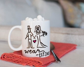 Customizable Mug: Your Chosen Last Name and Wedding Year under a whimsical, simplistic husband and wife couple. Handpainted on porcelain mug
