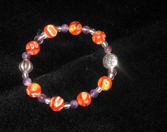 Orange, yellow, blue and white floral abstract glass beads with amethyst and silver bead stretch bracelet