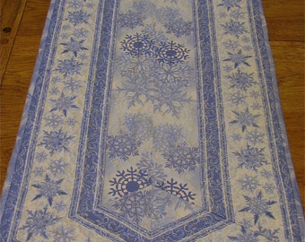 a handmade quilted blue and white winter snowflake table runner