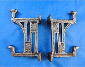 A pair of beautiful Arts and Crafts style cast iron Mackintosh coat hooks