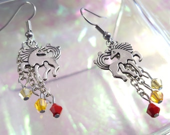 Unicorn in dangling earrings with red, yellow and amber beads.