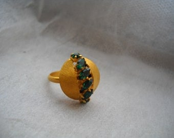 Early 70's adjustable French Ring. Gold plated, textured and adjustable. Row of Green Rhinestones displayed along the ring. Made in France
