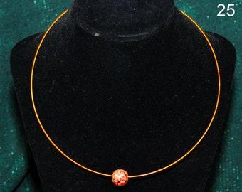 Pretty round plaid bead on a copper wire necklace.