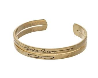 """Gold tone cuff bracelet stamped with """"Carpe Diem."""""""