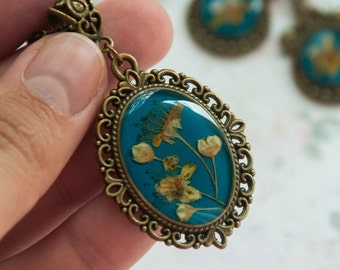 Handwork pendant with real wild flowers on a turquoise background. Exclusive handmade jewelry- gift for woman made out of nature materials!